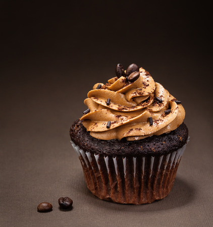 torta: Una taza de pastel de chocolate con glaseado de moca y rocía