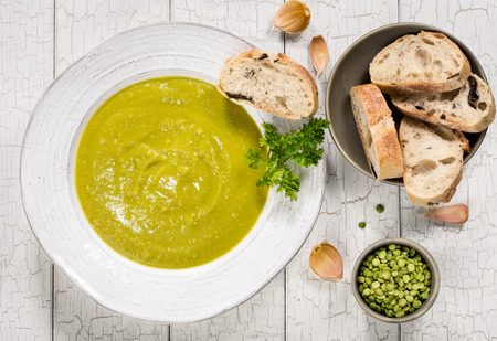 Close up of delicious homemade split pea soup with garlic, bread and parsley for garnish.