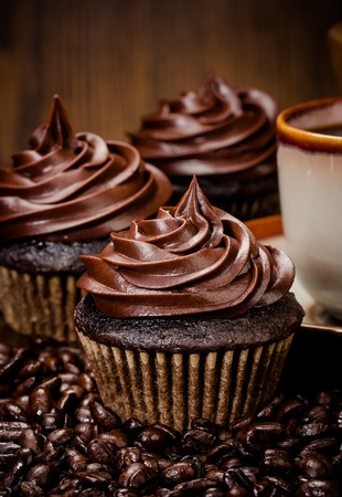 Three chocolate cupcakes with coffee  and beans