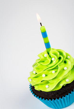 fairy cakes: Chocolate Cupcake decorated with green icing, sprinkles and a lit birthday candle on a white background.