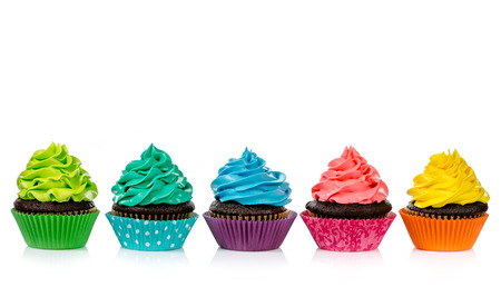 an icing: Chocolate cupcakes in a row with colorful icing on a white background.