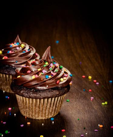 tortas de cumpleaños: Dos magdalenas del cumpleaños de chocolate con colorido asperja
