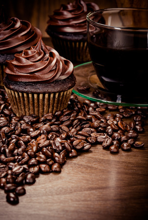 colombian food: Three chocolate cupcakes with coffee  and beans on wood Stock Photo