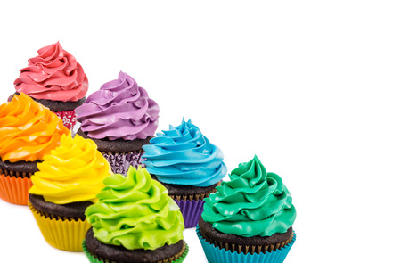 Chocolate cupcakes with colorful icing on a white background. Foto de archivo