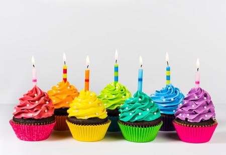 pasteles de cumpleaños: Filas de cup cakes decorados con coloridas velas de cumpleaños y rocía.