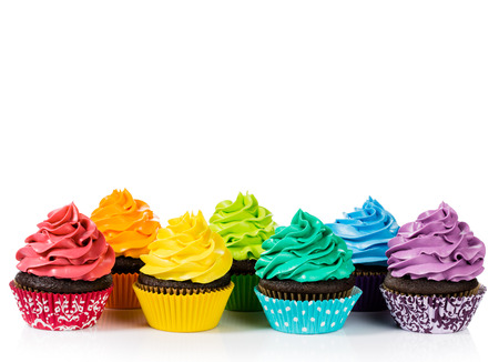 cakes background: Chocolate cupcakes in rows with colorful icing on a white background.