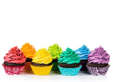 Schokoladen-Muffins in Reihen mit bunten Zuckerguss auf einem weißen Hintergrund.