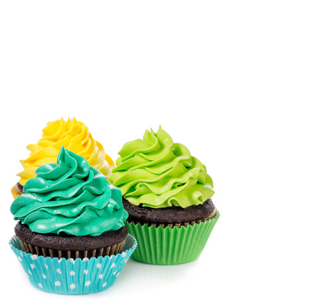 Chocolate cupcakes arranged with colorful icing on a white background. Banque d'images