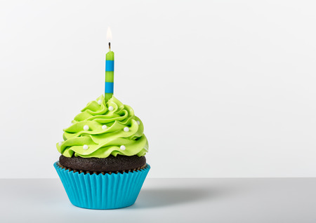 an icing: Chocolate Cupcake decorated with green icing, sprinkles and a lit birthday candle on a white background.