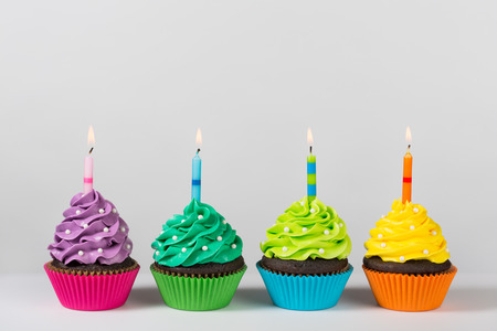 Four colorful cupcakes decorated with birthday candles and sprinkles.