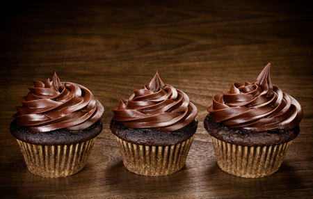 Three chocolate cupcakes in a row over a wooden background Banco de Imagens