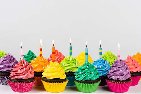 Rows of colorful cup cakes decorated with birthday candles and sprinkles.