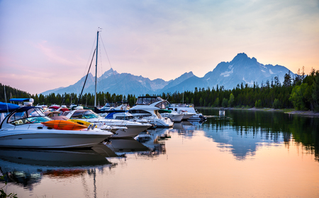 port jackson: Boats on the lake at sunset in Colter bay with majestic Grand Teton Mountains in the Background Stock Photo