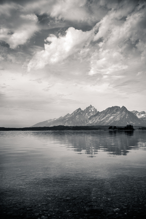 rocks water: Black and White view across Jackson Lake with the Grand Tetons in wyoming, USA.