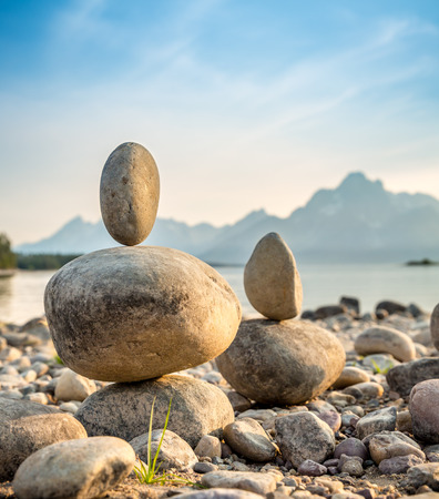 balanced rocks: Pure balanced rocks at sunset with lake and mountains in the background. Stock Photo