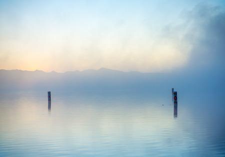 landschap: Dromerig waterlandschap met ochtendmist over kalme oppervlakte Stockfoto