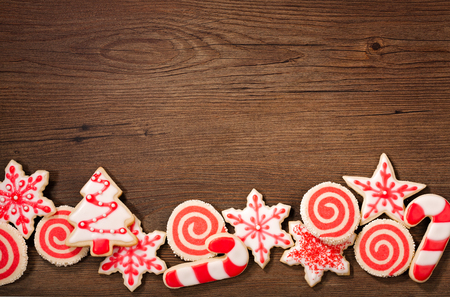 Overhead shot of a red and white Christmas cookies border on a wooden background.