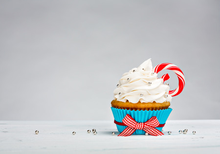 Christmas Cupcake with vanilla buttercream icing and a Candy Cane over a white background.