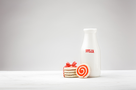 White milk bottle and red pinwheel cookies for Santa over a white background.