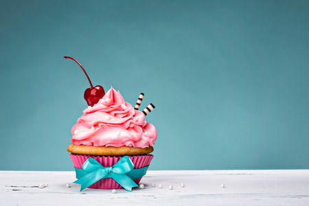 cakes background: Cupcake with pink buttercream icing and a cherry on top. Stock Photo