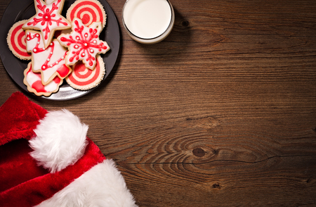 Eine Tasse Milch, Weihnachtsmütze und Weihnachtsgebäck auf einem Teller auf einem hölzernen Hintergrund.