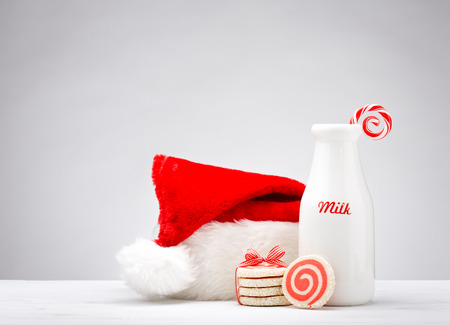 to santa: Milk bottle, pinwheel cookies and a candy cane for Santa over a white background. Stock Photo