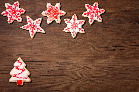 Overhead shot of a snow and Christmas tree cookies on a wooden background.