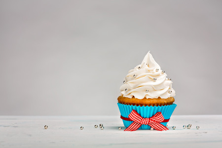 Vanilla Cupcake with buttercream icing over a light colored background.
