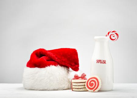 Milchflasche, pinwheel Cookies und eine Zuckerstange für Sankt über einem weißen Hintergrund. Standard-Bild - 46076093