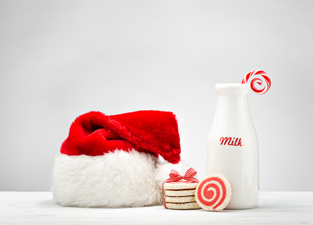 drink food: Milk bottle, pinwheel cookies and a candy cane for Santa over a white background. Stock Photo