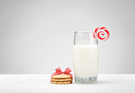 Glass of Milk with sugar cookies and a candy cane over a white background.