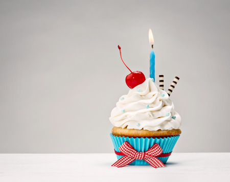 Cupcake with vanilla buttercream icing, birthday candle and a cherry on top. Foto de archivo