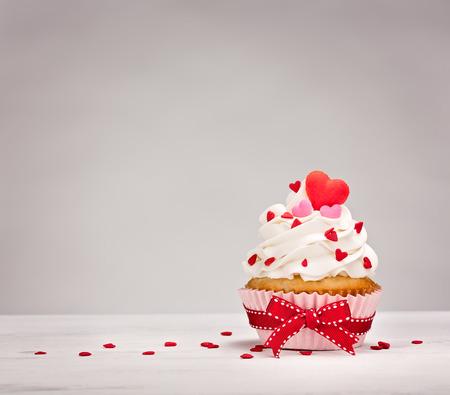 Vanille-Kuchen mit Buttercreme Zuckerguss, Herz geformt besprengt und einer roten Schleife.