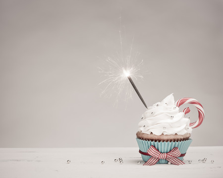 Christmas birthday Cupcake with a sparkler,  vanilla buttercream icing and a Candy Cane