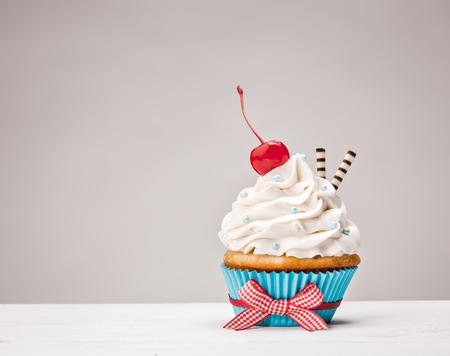 Cupcake mit Vanille Buttercreme Zuckerguss und eine Kirsche auf die Oberseite.