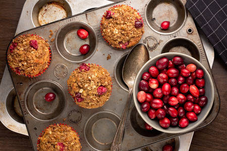 muffin: Freshly baked cranberry muffins with oatmeal crumble topping in a rustic muffin tin.