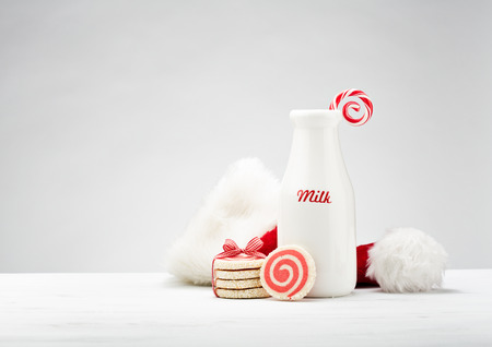 Milk bottle, pinwheel cookies and a candy cane for Santa over a white background. Stock Photo