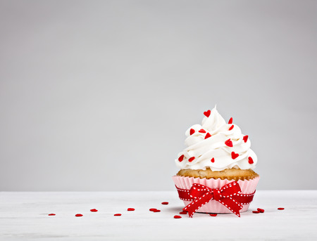 sweet: Vanilla Cupcake with buttercream icing, heart shaped sprinkles and a red bow.