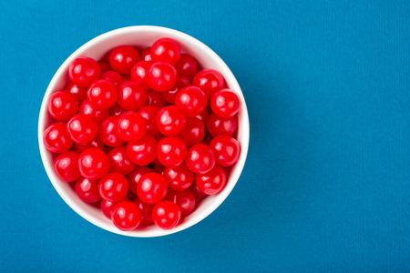 cereza: Tazón de dulces cerezas rojas sobre un fondo azul
