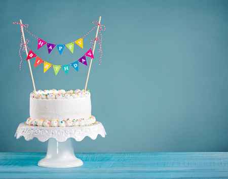 pastel de cumpleaños: Blanco crema de mantequilla tarta de cumpleaños con coloridos banderines y rocía sobre fondo azul