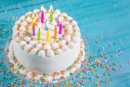 青い背景にカラフルなスプリンクル、キャンドルで誕生日ケーキを着氷ホワイト バター クリーム