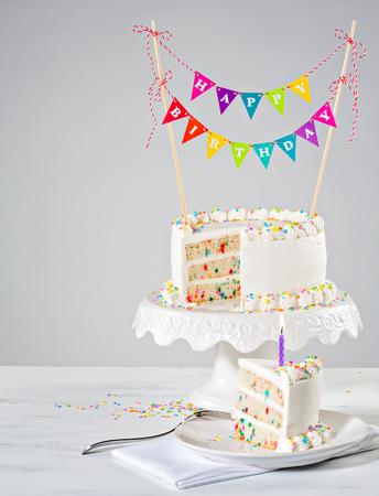 porcion de torta: Blanco crema de mantequilla tarta de cumpleaños con coloridos banderines y rocía sobre el fondo blanco Foto de archivo