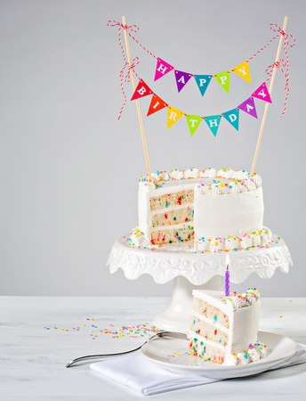 White Buttercream birthday cake with colorful bunting and sprinkles over white background