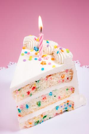 trozo de pastel: Rebanada de pastel de cumpleaños con colorido asperja y vela encendida