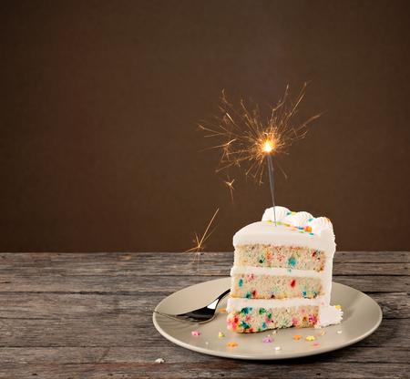Scheibe der Geburtstagstorte mit bunten Streuseln und beleuchteten Sparkler