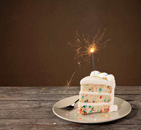 Slice of Birthday Cake with colorful sprinkles and lit sparkler Stock Photo