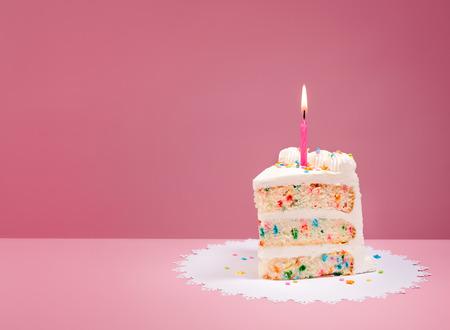 Rebanada de la torta de cumpleaños colorida de confeti con una vela encendida sobre un fondo de color rosa.
