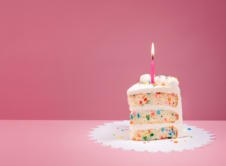 Slice of Colorful Birthday Confetti Cake with a lit candle over a pink background.
