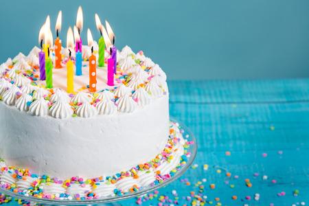 Blanco crema de mantequilla tarta de cumpleaños con la formación de hielo con virutas de colores y velas sobre fondo azul