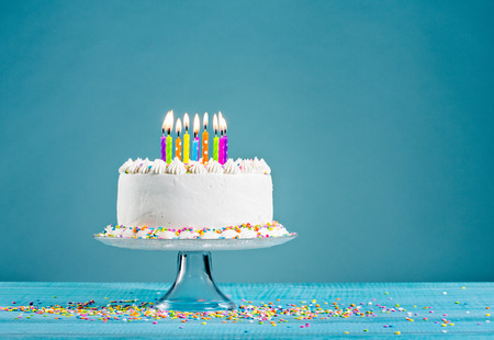 pastel cumpleaños: Blanco crema de mantequilla tarta de cumpleaños con la formación de hielo con virutas de colores y velas sobre fondo azul